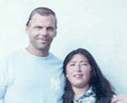 Photo of parole violator Joe David Allums, II and dark-haired woman